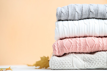 Stack of folded sweaters with maple leafs on beige background