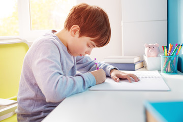 nine years old child writing at home. Boy studying at table on blue background. Kid drawing with a pencil