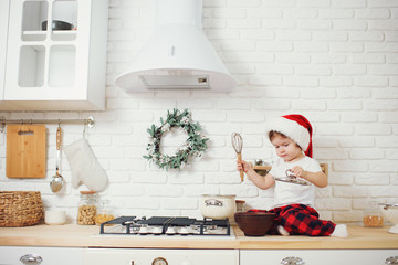 Cute little girl in santa hat, preparing cookies in the kitchen at home. Sits on the kitchen table and helps mom prepare a festive Christmas dinner