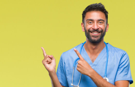 Adult hispanic doctor or surgeon man over isolated background smiling and looking at the camera pointing with two hands and fingers to the side.