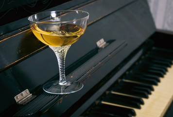 Alcoholic drink in glass on the piano