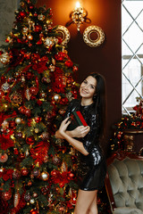 The concept of the Christmas party. Young brunette woman in a short black dress in sequins smiling and holding a gift on the background of a beautifully decorated room with a Christmas tree.