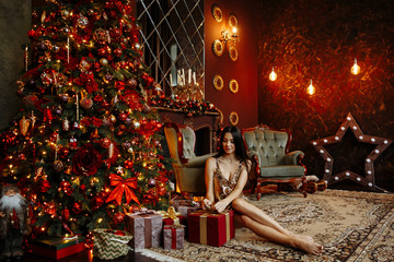 Christmas party. A young brunette woman in a gold dress in sequins smiles and opens Christmas gifts on the background of a beautifully decorated room with a fireplace and a Christmas tree.