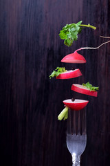 Pieces of fresh radish and cilantro are flying against the dark background