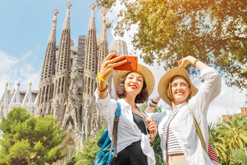 Zelfklevend Fotobehang Barcelona BARCELONA, SPAIN - 11 JULY 2018: Young girls friends making selfie photo on her smartphone in front of the famous Sagrada Familia catholic cathedral. Travel in Barcelona concept