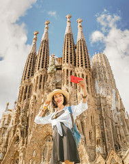 Foto op Canvas Barcelona BARCELONA, SPAIN - 11 JULY 2018: Young asian woman making selfie photo on her smartphone in front of the famous Sagrada Familia catholic cathedral. Travel in Barcelona concept