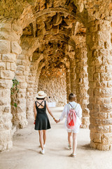 Two happy traveler women tourists walking in famous Guell park in Barcelona