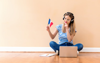 Young woman with French flag using a laptop computer against a big interior wall Wall mural