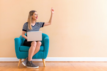 Young woman with a laptop computer pointing something in a chair