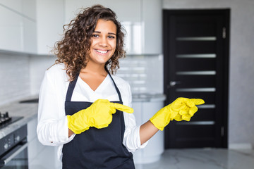 Pretty young latin cleaning lady pointing fingers at blank white board with kitchen in background