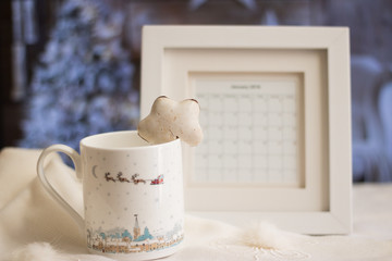 Close-up: mug and Christmas gingerbread on a white winter scarf. A blurred image of frame calendar is also on the table against background of a beautiful festive room with a decorated Christmas tree.