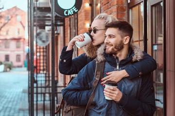 A beautiful girl hugs her boyfriend near the cafe outside.