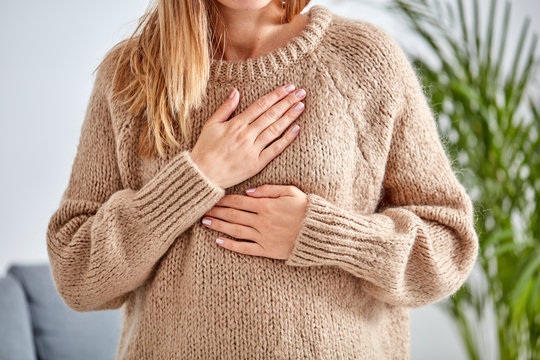 Young woman with heart problem holding chest.
