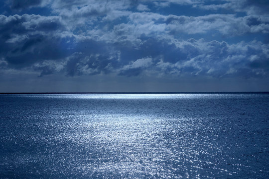 sea and sky with shimmering ocean lit by moonlight