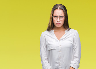 Young caucasian beautiful business woman wearing glasses over isolated background skeptic and nervous, frowning upset because of problem. Negative person.