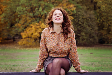 jeune et jolie femme rousse souriant assise sur un banc dans un parc en automne