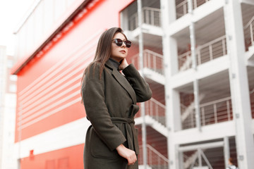 Young pretty stylish girl with sunglasses in a vintage fashionable coat walks in the city