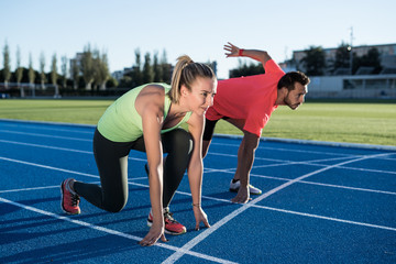 Athlete couple at starting position ready to start a race. Sprinters ready for race on race track. Woman against man.