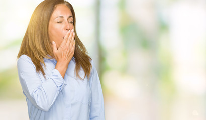 Beautiful middle age business adult woman over isolated background bored yawning tired covering mouth with hand. Restless and sleepiness.