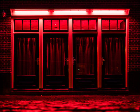 Red Light District in Amsterdam. Red boxes with curtains and wet Cobbles on the street