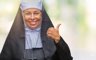 Middle age senior christian catholic nun woman over isolated background smiling with happy face looking and pointing to the side with thumb up.