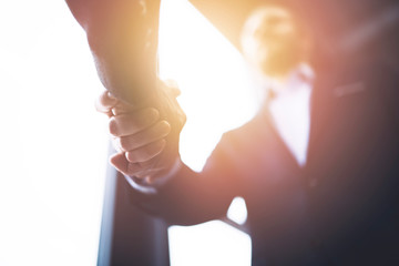 Handshaking business person in the office with network effect. concept of teamwork and partnership
