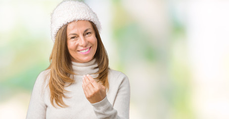Beautiful middle age woman wearing winter sweater and hat over isolated background Beckoning come here gesture with hand inviting happy and smiling