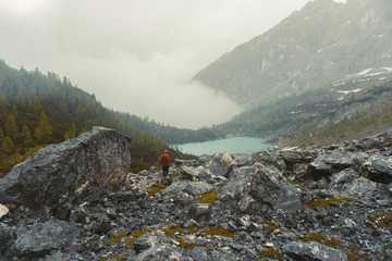 Tall hiker with backpack. Rocky part of path with view into distance. Foggy forest landscape in morning sun. Fantastic areial view into forest landscape
