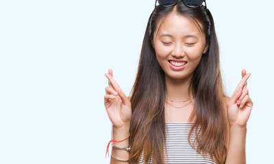 Young asian woman wearing sunglasses over isolated background smiling crossing fingers with hope and eyes closed. Luck and superstitious concept.