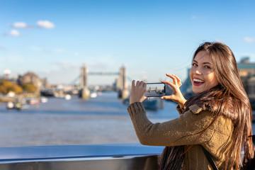 Portrait einer glücklichen Touristin in London beim Fotografieren der Tower Bridge auf ihrer Sightseeing Tour durch die Stadt