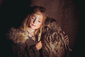 Girl in the style of boho with an owl. Boho chic hugs big owl