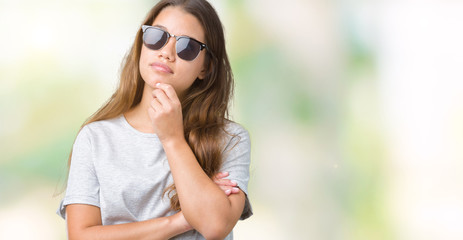 Young beautiful brunette woman wearing sunglasses over isolated background with hand on chin thinking about question, pensive expression. Smiling with thoughtful face. Doubt concept.