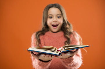 Child enjoy reading book. Book store concept. Wonderful free childrens books available to read. Childrens literature. Useful information for her. Girl hold book read story over orange background
