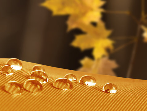 Waterproof fabric with waterdrops close up on a background of a autumn landscape