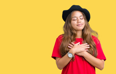 Young beautiful brunette fashion woman wearing red t-shirt and black beret over isolated background smiling with hands on chest with closed eyes and grateful gesture on face. Health concept.