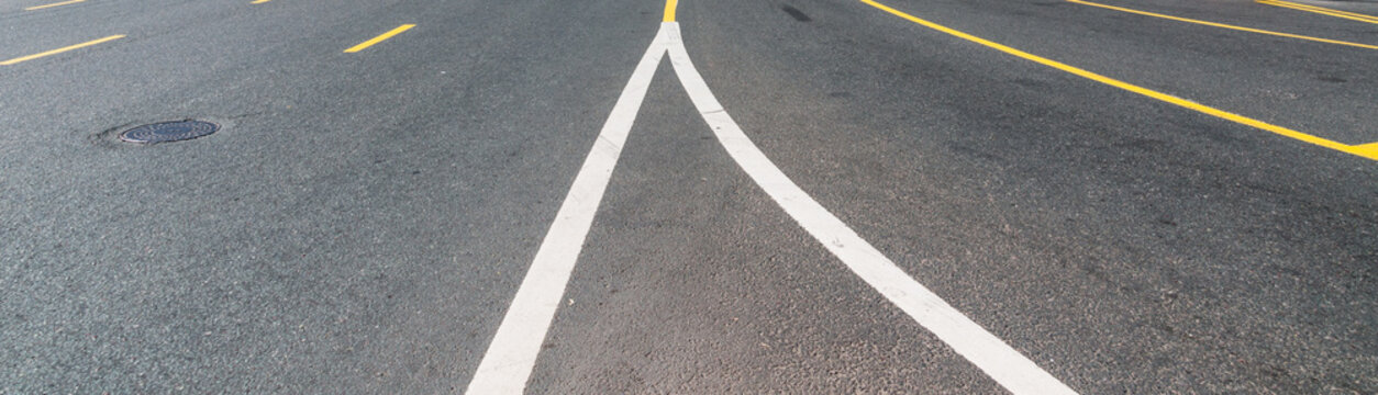 Road with white and yellow road markings and sewer hatch