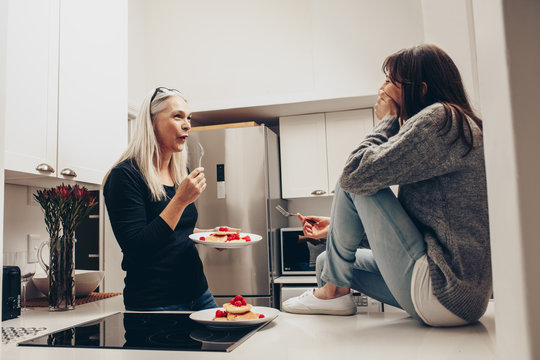 Mother and daughter sitting in kitchen eating cookies