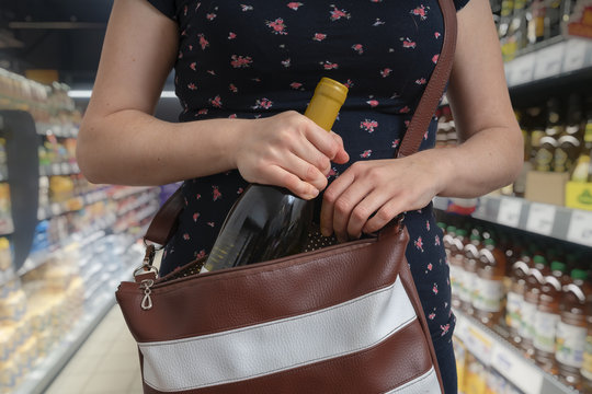 Woman is stealing bottle of wine and hiding it in handbag in sup