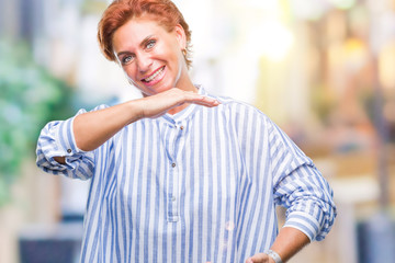 Atrractive senior caucasian redhead woman over isolated background gesturing with hands showing big and large size sign, measure symbol. Smiling looking at the camera. Measuring concept.