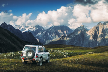 Landscape view of mountain range and offroad car in the meadow, Svaneti, Country of Georgia
