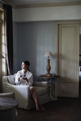 Beautiful Asian woman drinking tea at hotel room.