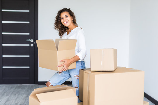 Happy smiling mixed race woman carrying carton boxes moving to new apartment