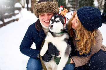 Family portrait of cute happy couple hugging with their alaskan malamute dog licking man's face. Funny puppy wearing santa christmas deer antlers. Freedom lifestyle pet lovers young family smiling.