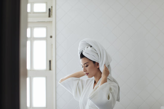 Portrait of beautiful Thai woman wearing a bathrobe and a towel on her head.