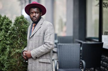 Stylish African American man model in gray coat, jacket tie and red hat.