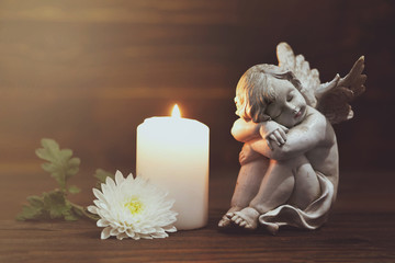 Angel, white flower and burning candle