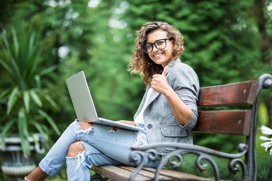 Mixed race woman in eyeglasses sitting on the bench in park with laptop computer and showing thumb up