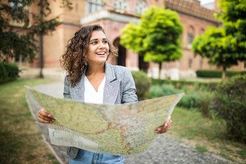 Travel guide. Tourism in Europe. Latin american woman tourist with map on the street