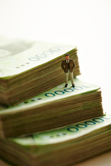 Miniature man with Korean won banknotes