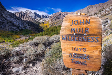 Sign posted at the entrance to the John Muir Wilderness, in the Inyo National Forest; Eastern Sierra mountains, California; McGee valley visible in the background; beautiful sunny fall day Fototapete